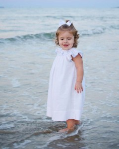 Connie's granddaughter Maddie modeling her sea shell dress by Petit Bebe.